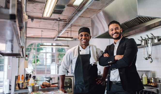business owner and chef inside kitchen of restaraunt