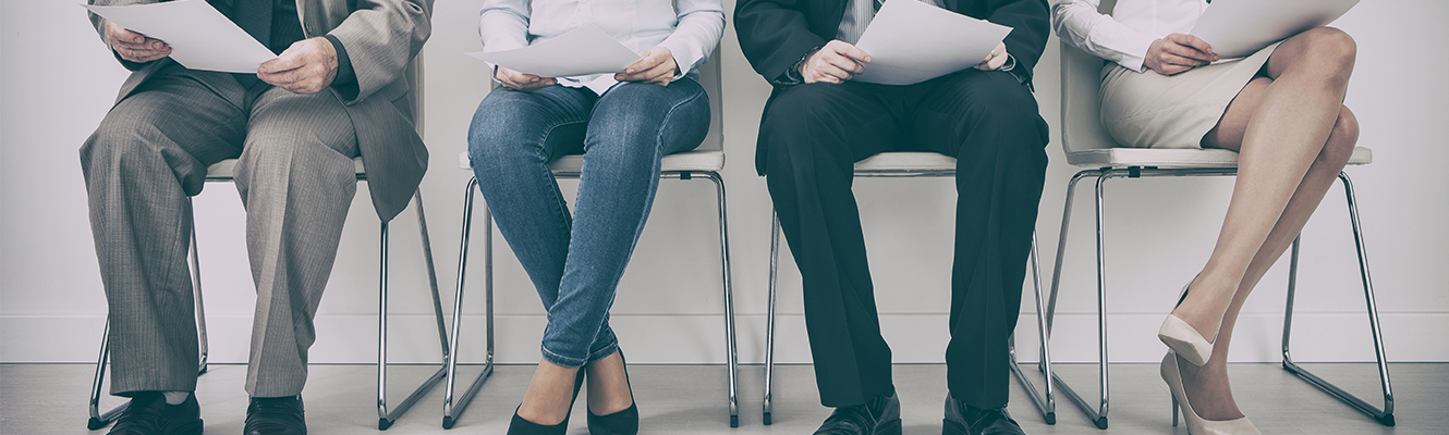 Men and Women sitting in Chair with Resumes